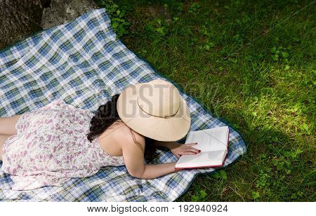 Woman reading a book outside in the grass