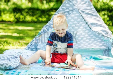 A little kid laughs and reads a book in the park. Boy preschool. The concept of childhood learning and lifestyle.