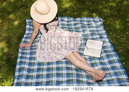 Woman reading a book outside in the grass on a blanket