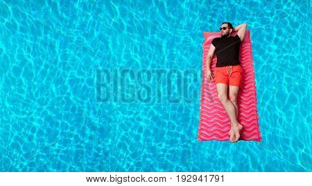Summer Vacation. Enjoying suntan. Man in t-shirt and shorts on the inflatable mattress in the swimming pool.