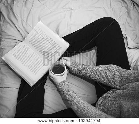 Relaxed woman in the morning.  Woman reading a book and drinking coffee in bed.  Black & white photograph.