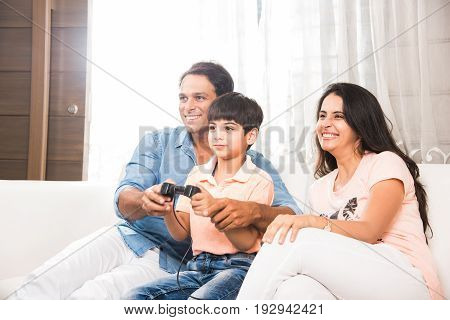 Family time - Happy Indian family- father, mother and son playing a video game at home. Asian family playing video game with joy stick or controller