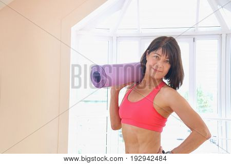 Mature woman holding rolled up exercise mat at gym. Cheerful female fitness instructor holding mat