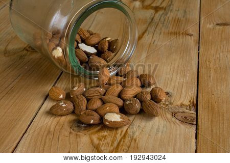 Tasty almonds in bowl on wood table