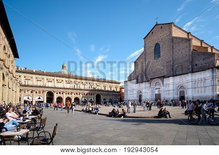 Bologna Italy - April 17 2017: Citizens and tourists on a sunny day walk and relax in Piazza Maggiore Bologna's main square in front of the church of San Petronio a place full of historic monuments and city center.