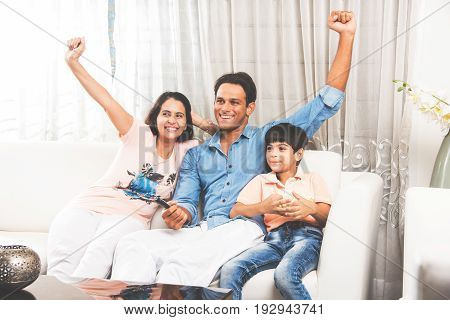 Indian young Family of 4 Sitting On Sofa while Watching TV Together, selective focus