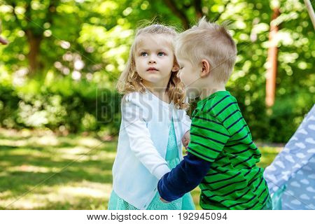 Brother and sister walk in the park. Preschool children. 2-3 years. The concept is childhood and family.