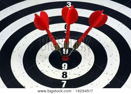 Three red darts hitting a target board, concept for success