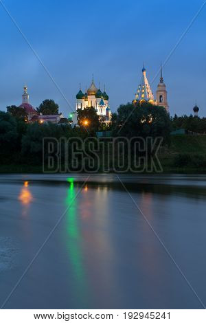 Kolomna Moscow Region. Various Temples And Belltower On Assumption Cathedral Square In Bright Illumination Under Blue Sky. Beautiful View From River's Embankment.