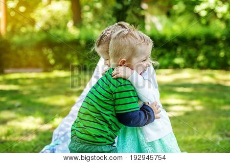 Children hug in the park. 2-3 years. Girl and boy. The concept is childhood and family.