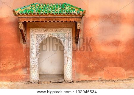 Typical decorated Moroccan door with green roof and ethnic handmade decoration. Rough wall with small multicolor port entrance in Arabic style decoration. Concept of freedom to travel around world.