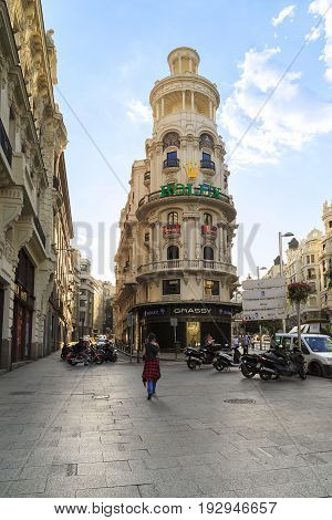 MADRID, SPAIN - MAY 24, 2017: The Grassi Building with a round corner facade and a two-tier tower with columns is one of the most famous buildings on Gran Via.