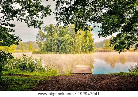 Morning landscape on the lake. Wooden pier and islet with trees on the lake.