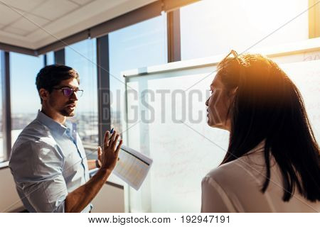 Business colleagues involved in a discussion in boardroom. Businessman presenting business plans on whiteboard.