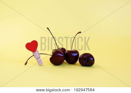 Cherry and clothespin on a yellow background, close up
