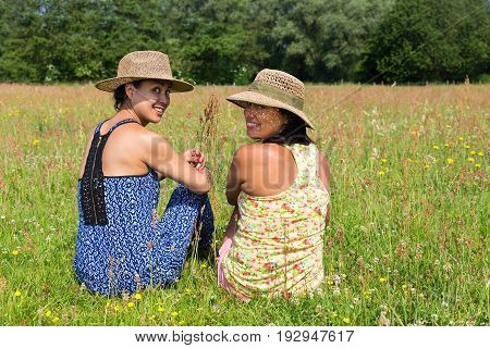 Two friends with hats looking back in blooming meadow