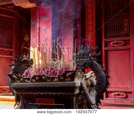 Burning red chinese candle in temple on light wind