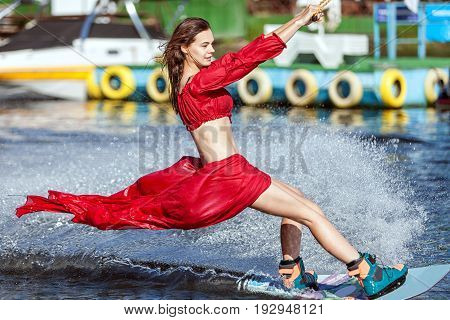 Woman in a red dress does not wakeboard. Her dress is blown by the wind.