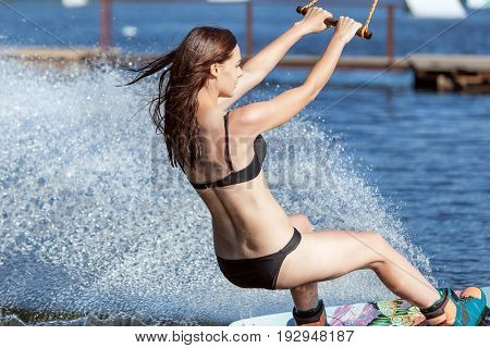 Woman in a bathing suit skates on the lake on wakeboarding.