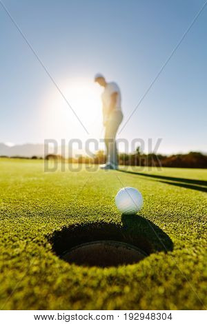 Vertical shot of professional golfer putting golf ball in to the hole. Golf ball by the hole with player in background on a sunny day.