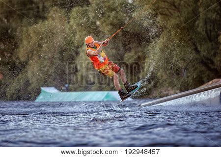 Man jumps on the water on a wakeboard he is an extreme sportsman.
