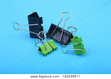 Close-up with Set of color clerical clips for paper on blue background