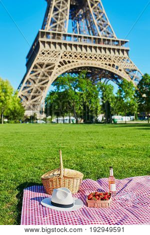 Beautiful picnic set with basket pink wine strawberries and glasses on the grass near the Eiffel tower Paris France