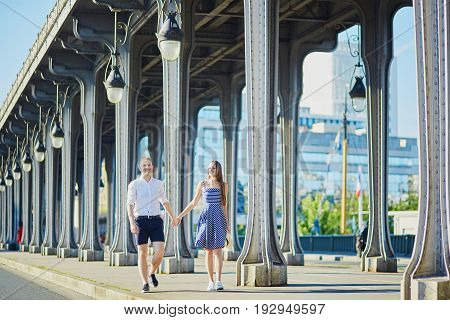 Couple Walking Along Bir-hakeim Bridge In Paris, France