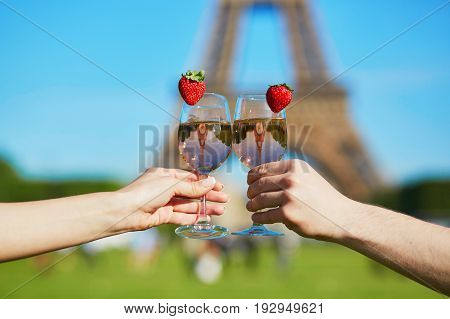 Couple Holding Glasses With Wine In Front Of The Eiffel Tower
