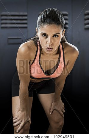 young attractive sexy latin sport woman posing in fierce and badass face expression with fit slim body isolated on gym locker room sweating in healthy lifestyle and fitness concept