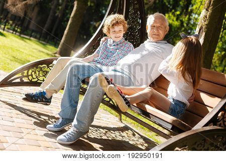 Sunny day. Positive delighted grandfather keeping smile on his face while sitting between his grandchildren on the swing and embracing them