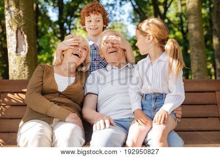 Keep smiling. Red haired boy standing behind his grandparents while putting hands on their eyes and looking at his little sister
