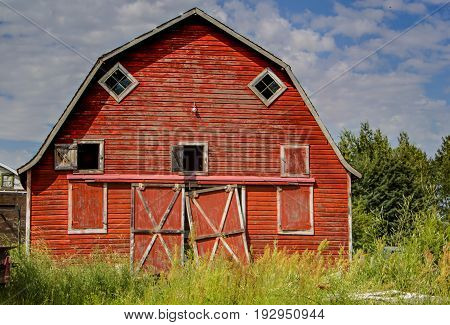 front facade of an old red barn with broken doors