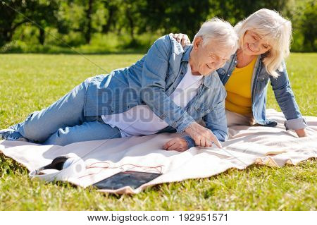 Reading book. Smiling old man lying on the plaid and leaning on the left elbow while looking downwards