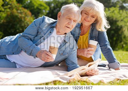 Coffee break. Pretty woman keeping smile on her face and holding paper cup in right hand while sitting behind her husband