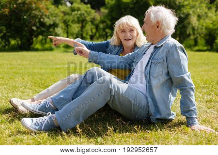 Casual style. Positive man sitting in semi position on the grass leaning on left hand and looking forward