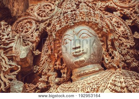 Face of Shiva Lord sculpture on wall of old relief. 12th centur Hindu Hoysaleshwara temple in Halebidu, India.
