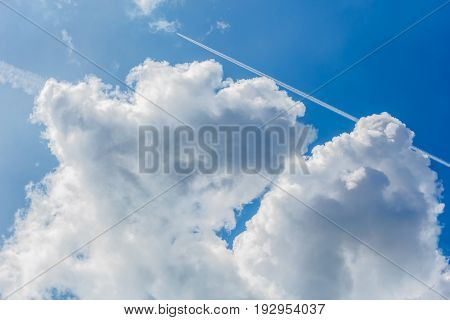 Blue sky with white cumulus clouds and contrails on a summer day close-up
