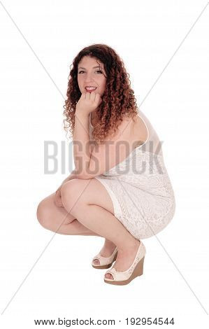 A beautiful young woman in a white dress crouching on the floor with one hand under her chin isolated for white background.