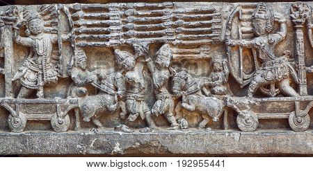 Artistic reloief with warriors scene and army of soldiers with bow arrows and other weapon. Artwork of 12th century Hoysaleshwara temple in Halebidu, India