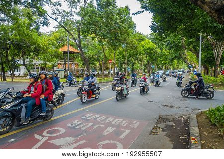 BALI, INDONESIA - MARCH 08, 2017: Unidentified people driving motorcycles and cars in the road full of traffic. The government says Bali streets could be gridlocked in five years with vehicle sales growing by 12.3 percent a year, in Denpasar Indonesia.