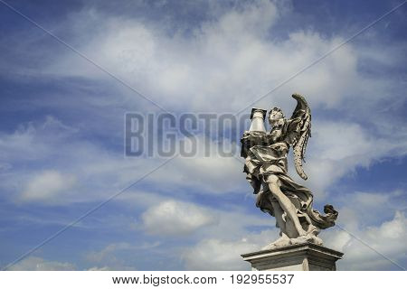Angel statue holding the Holy Column with heavenly sky on Sant'Angelo Bridge in the center of Rome