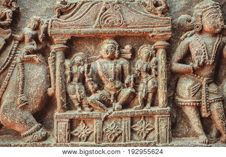 King or a reach man sitting on sculpured stone relief carvings from the 12th century temple's wall, Halebidu town of Karnataka. Old Indian artwork.