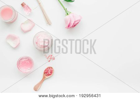 spa set with rose flowers and cosmetic for body care on white desk background top view mockup