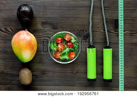 Slimming concept. Fruits, measuring tape and skipping rope on wooden table top view.