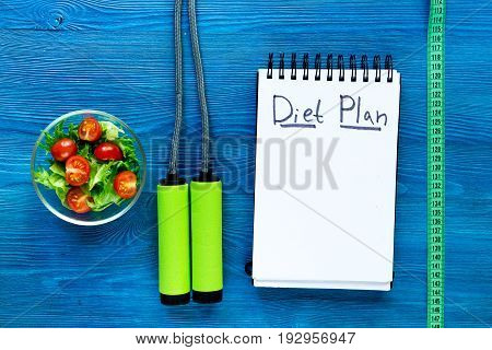 Heathy food for slimming. Notebook for diet plan, salad and measuring tape on wooden table top view mock up.