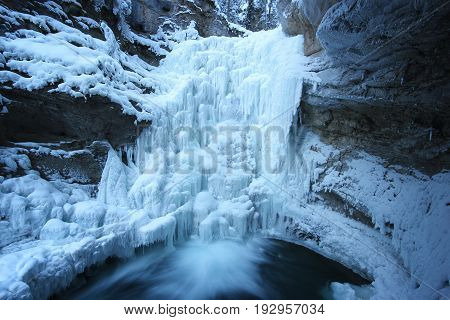 Fast flowing water from biig frozen waterfall with snow covered rocks around, Johnston Canyon, Banff National Park, Canada