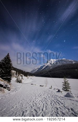 Frozen lake and snowy path in mountains during cold night under sky full of stars and faslty flowing clouds, Two Jack Lake, Banff, Canada