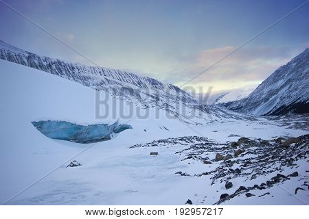 Big cold and blue ice cave in athabasca glacier, during gentle sunset, Banff national park, Canada