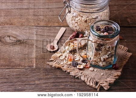 Glass jar of healthy gluten free muesli with nuts seeds and dried berries over rustic wooden background. Clean eating Healthy living Vegan Vegetarian Gluten free food concept